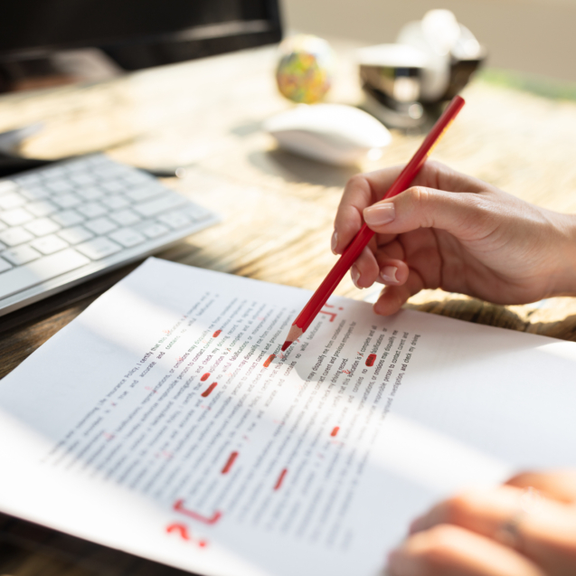 Close-up Of A Person's Hand Marking Error With Red Marker On Document
